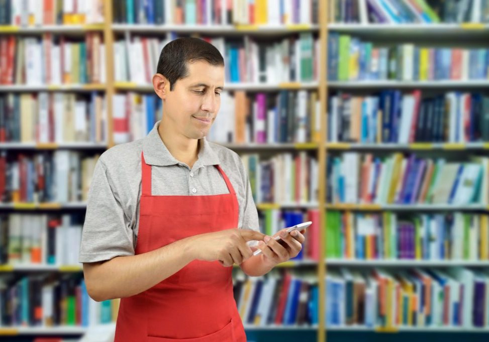 shop man with apron uses a smartphone at bookshop
